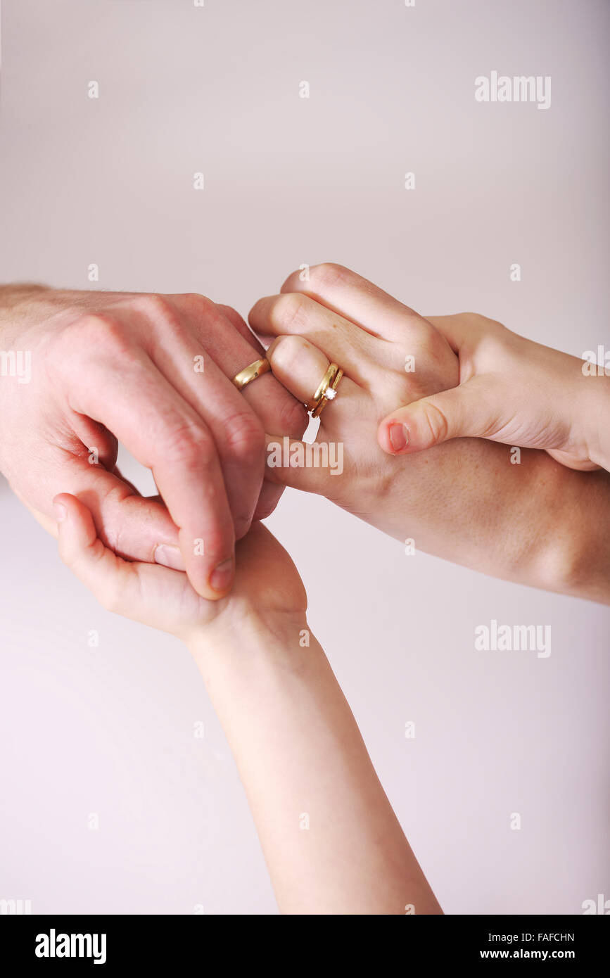 Young married couple grip onto each other as children's hands grip to both of them holding the relationship - Stock Image