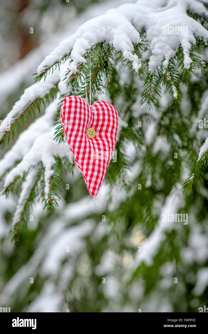 greeting card with handmade valentine heart from textile on the christmas tree with snow - Stock Image