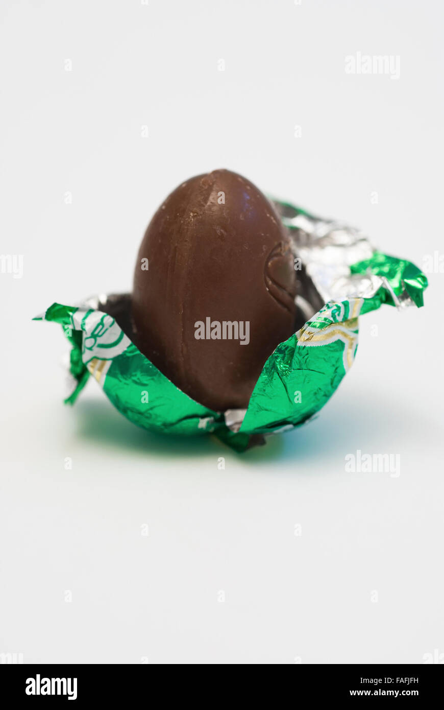 chocolate egg in foil half unwrapped - Stock Image