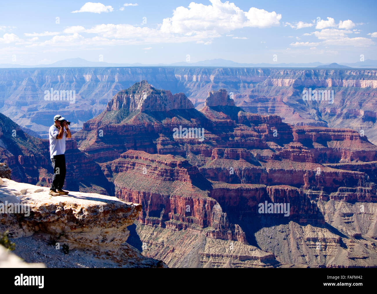 Man looking out over the Grand Canyon with binoculars, Arizona - Stock Image