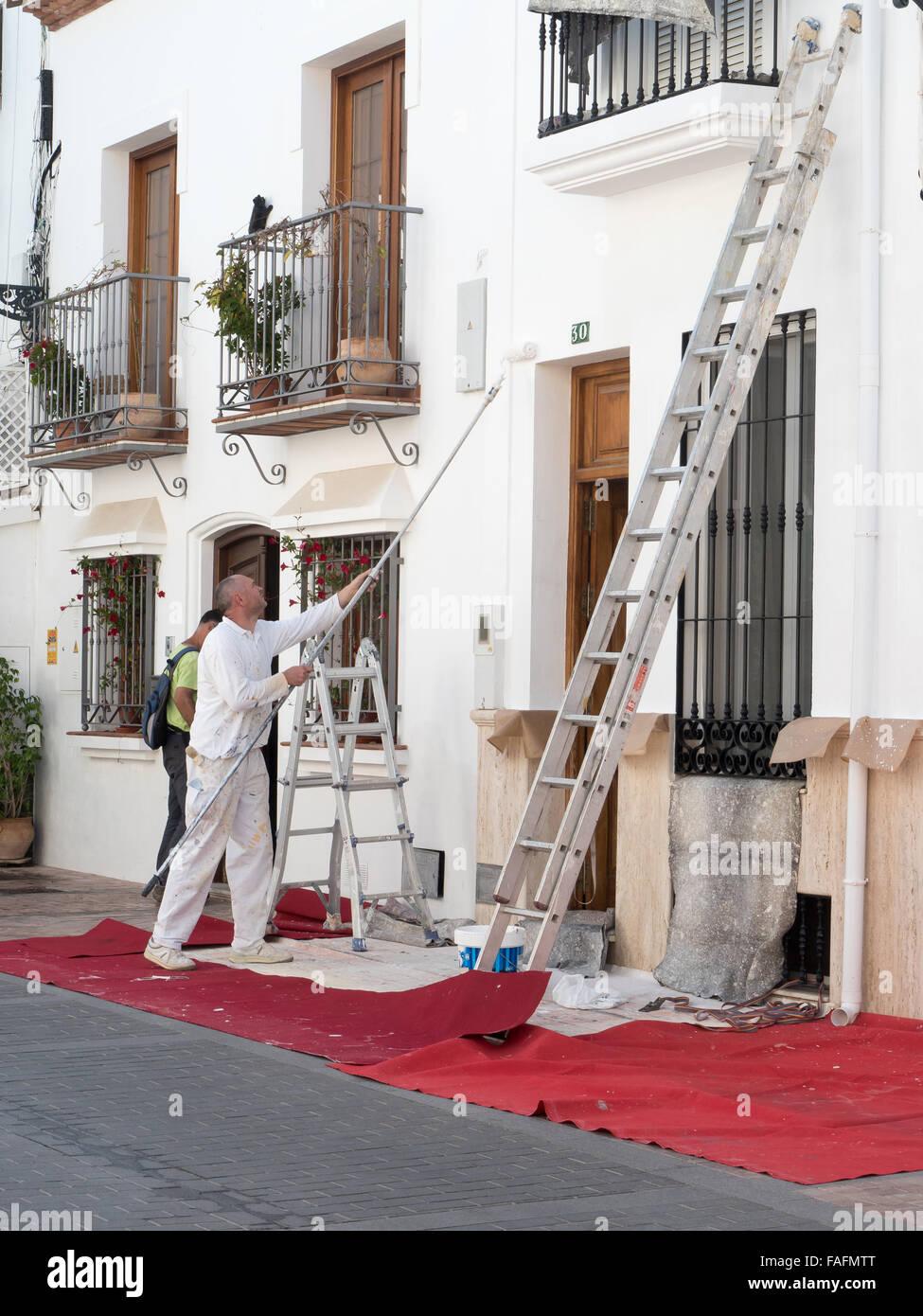Decorator Whitewashing Outside of Building, Nerja, Costa Del Sol, Spain, - Stock Image