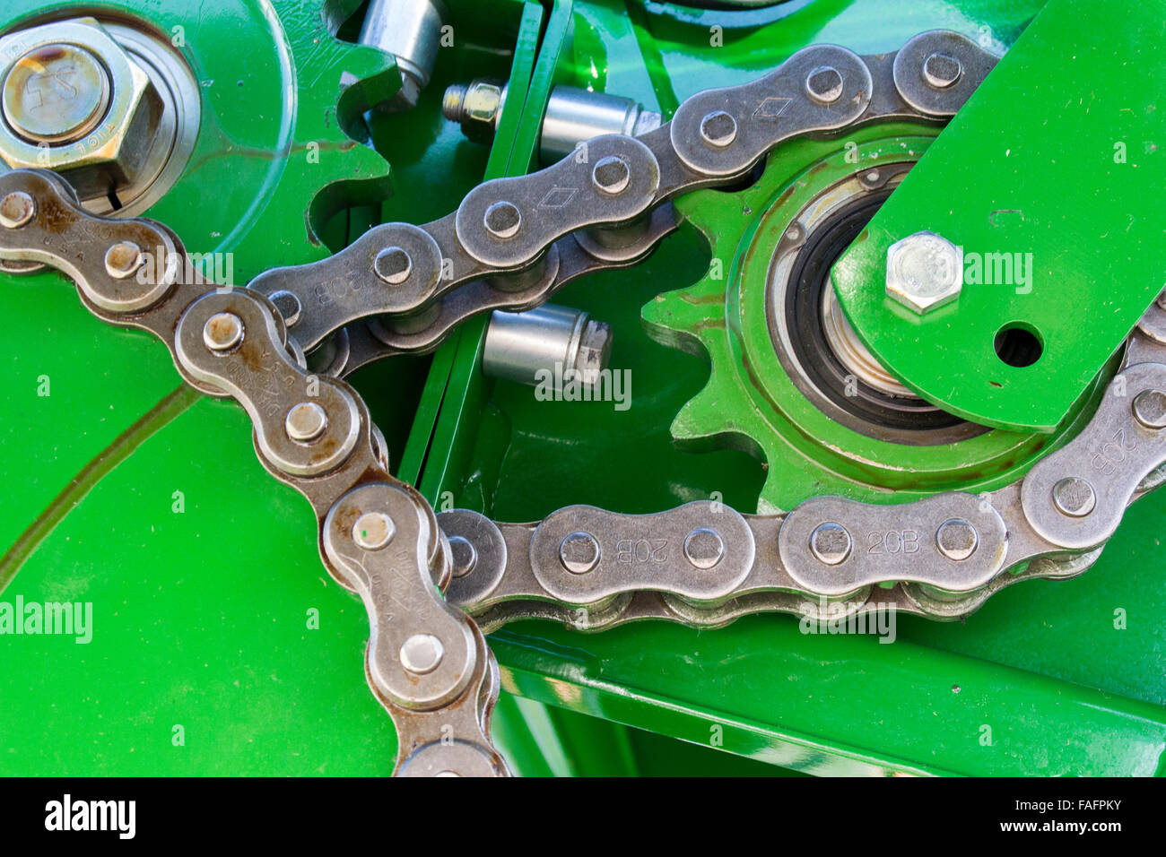 Internal workings of a big baler, showing cogs and chains. - Stock Image