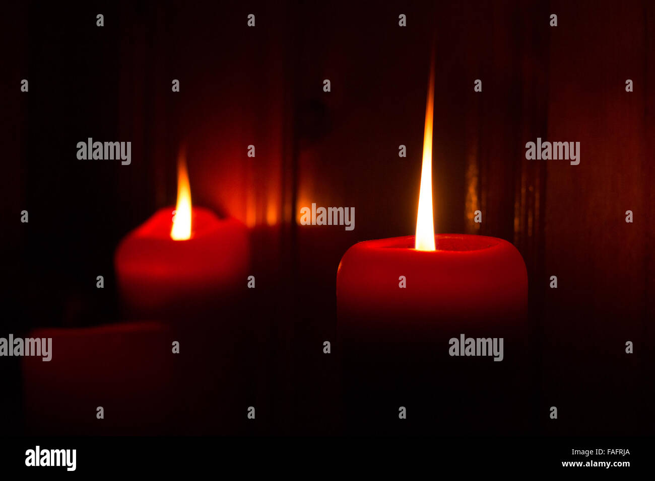 3 red burning candles lighting the darkness. - Stock Image