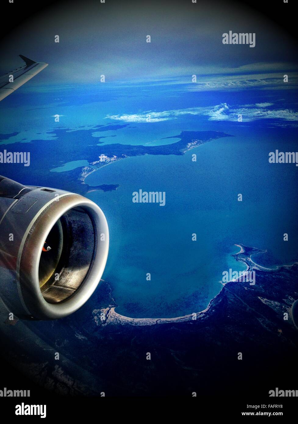 jet plane wing and engine flying over islands in the ocean, - Stock Image