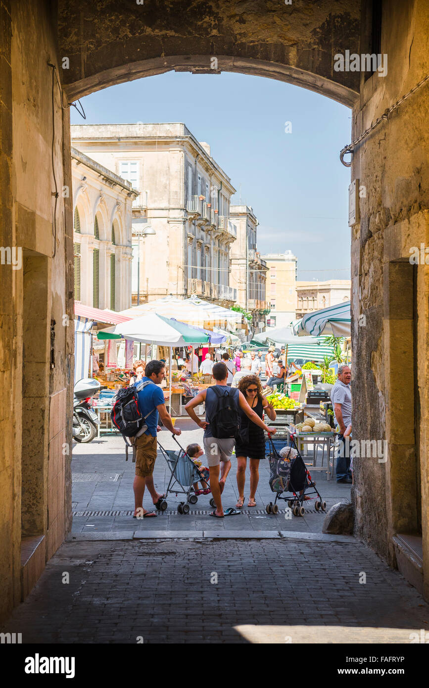 Italy family, parents with their children stand chatting during a shopping trip to the market in Syracuse, Sicily. - Stock Image