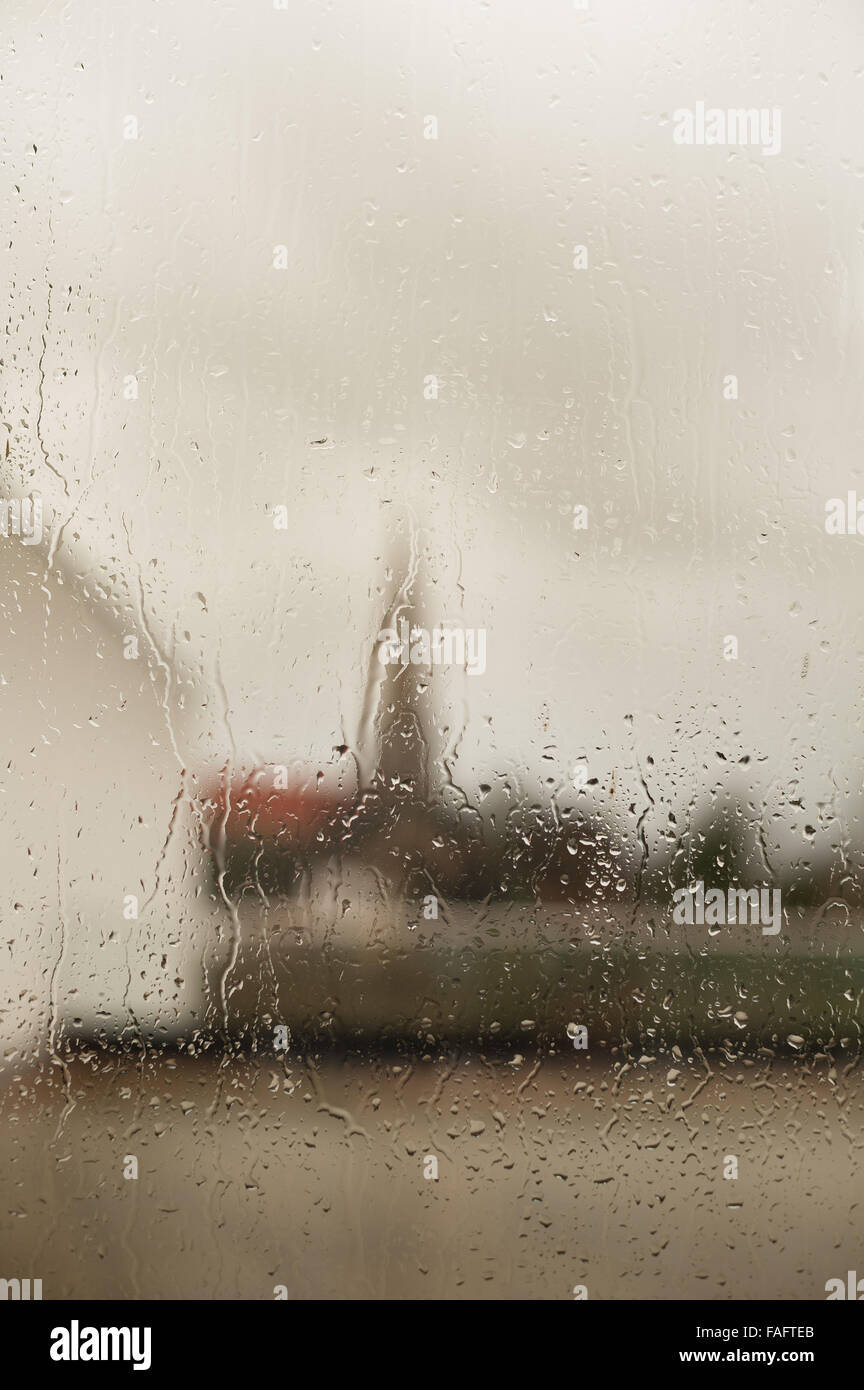 church and spire of church against skyline looking out from very wet rainy window with drops droplets running down - Stock Image
