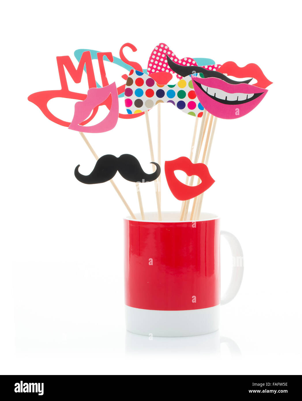 Photo Booth Props in a Red Mug on a White Background - Stock Image