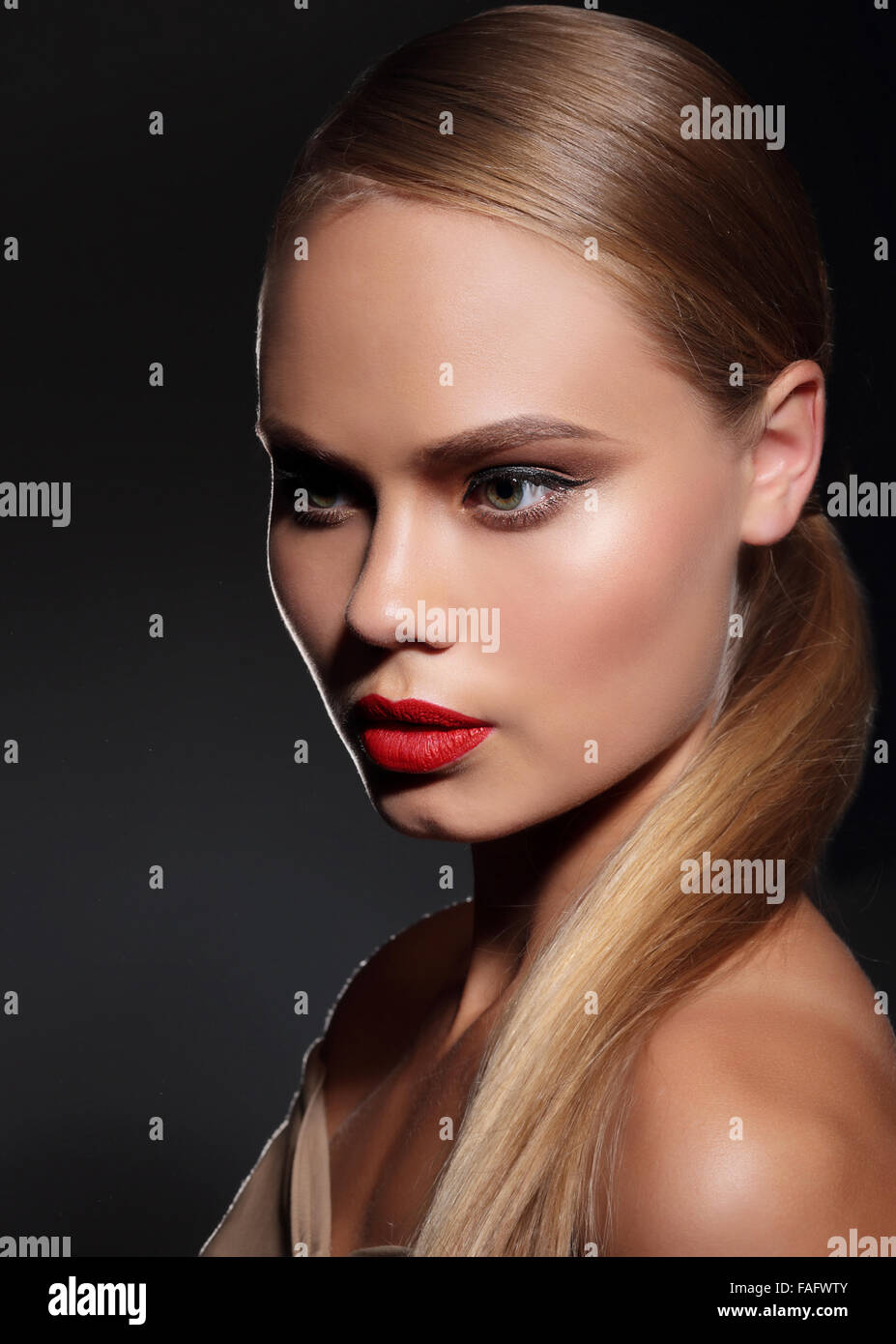 Young woman with straight hair and and red lips on dark background. Portrait. - Stock Image