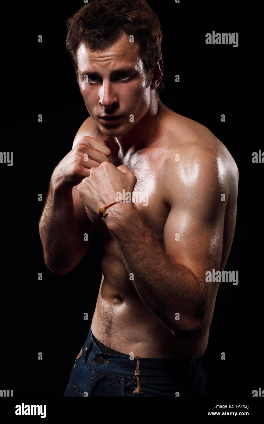 Portrait of muscular man with fighting stance against black background. - Stock Image