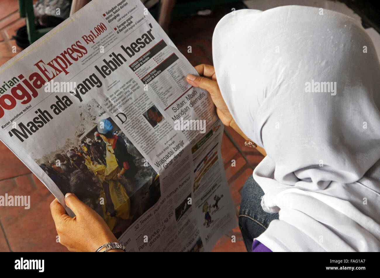 A woman reads the newspaper about the nearby Mount Merapi erupting volcano - Stock Image