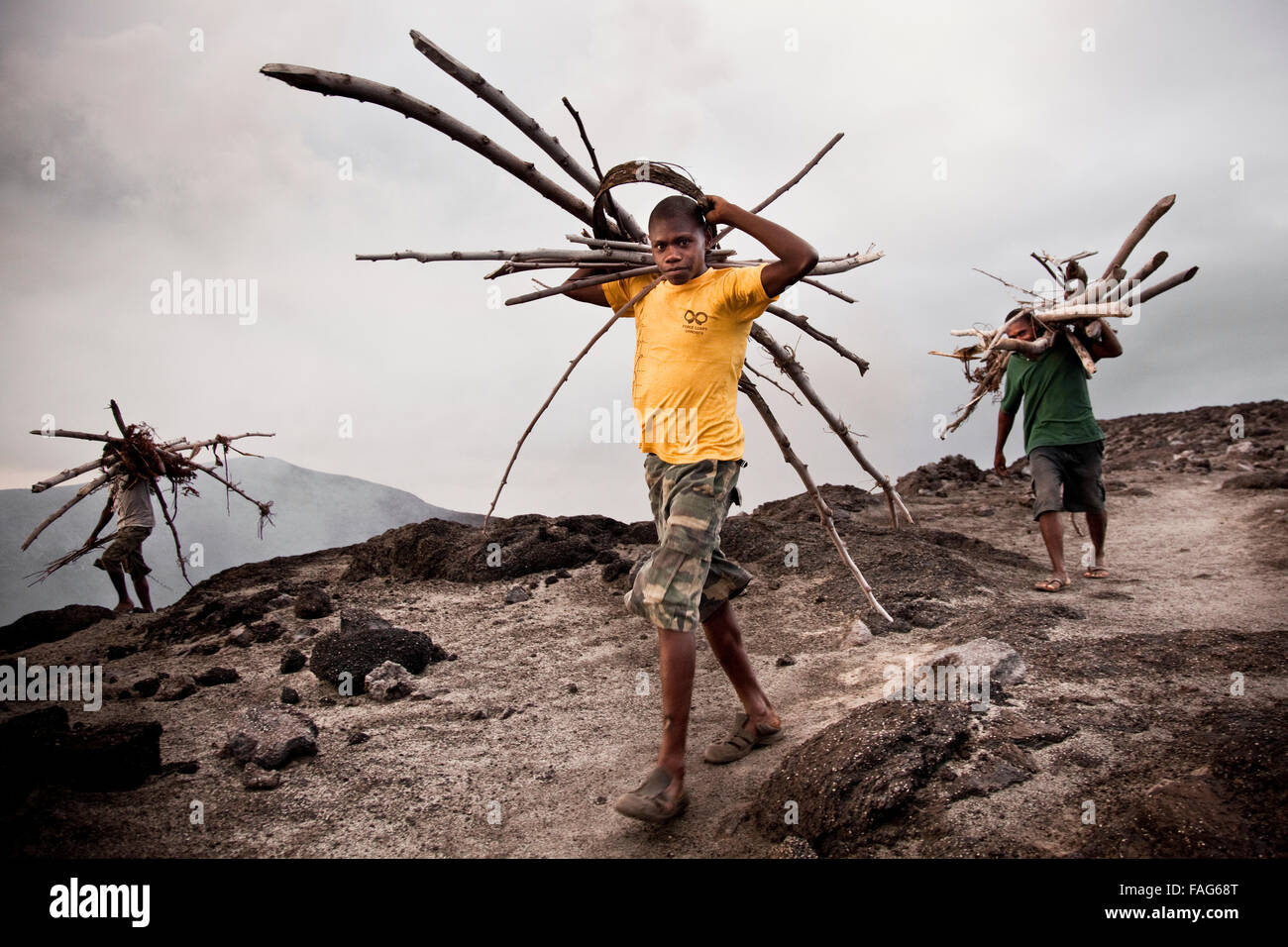 Local NiVans collecting firewood for a magma-started fire on Mt Yasur, an active volcano on Vanuatu's southern - Stock Image