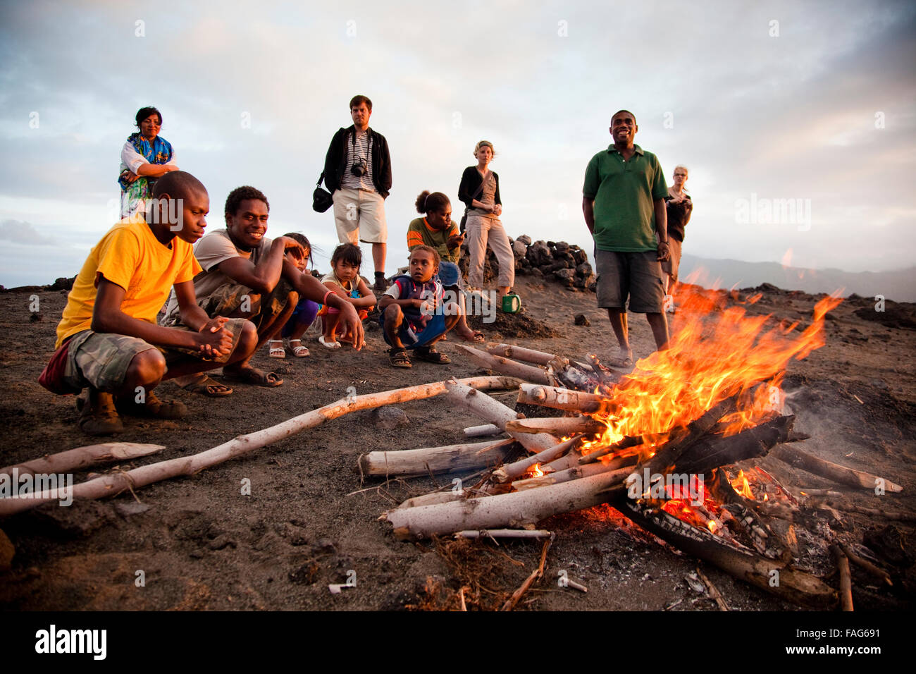 Tourists and local Nivans keep warm by a magma-started fire on Mt Yasur, an active volcano on Vanuatu's southern - Stock Image