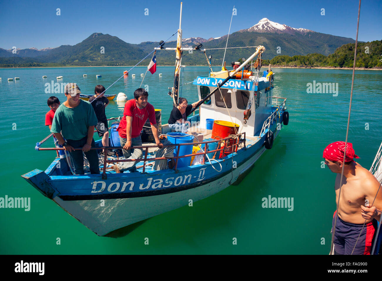 Fishing family aboard Don Jason II in Chile's Reloncaví Sound. Volcano Mt Yates rises 2111m above sea level - Stock Image