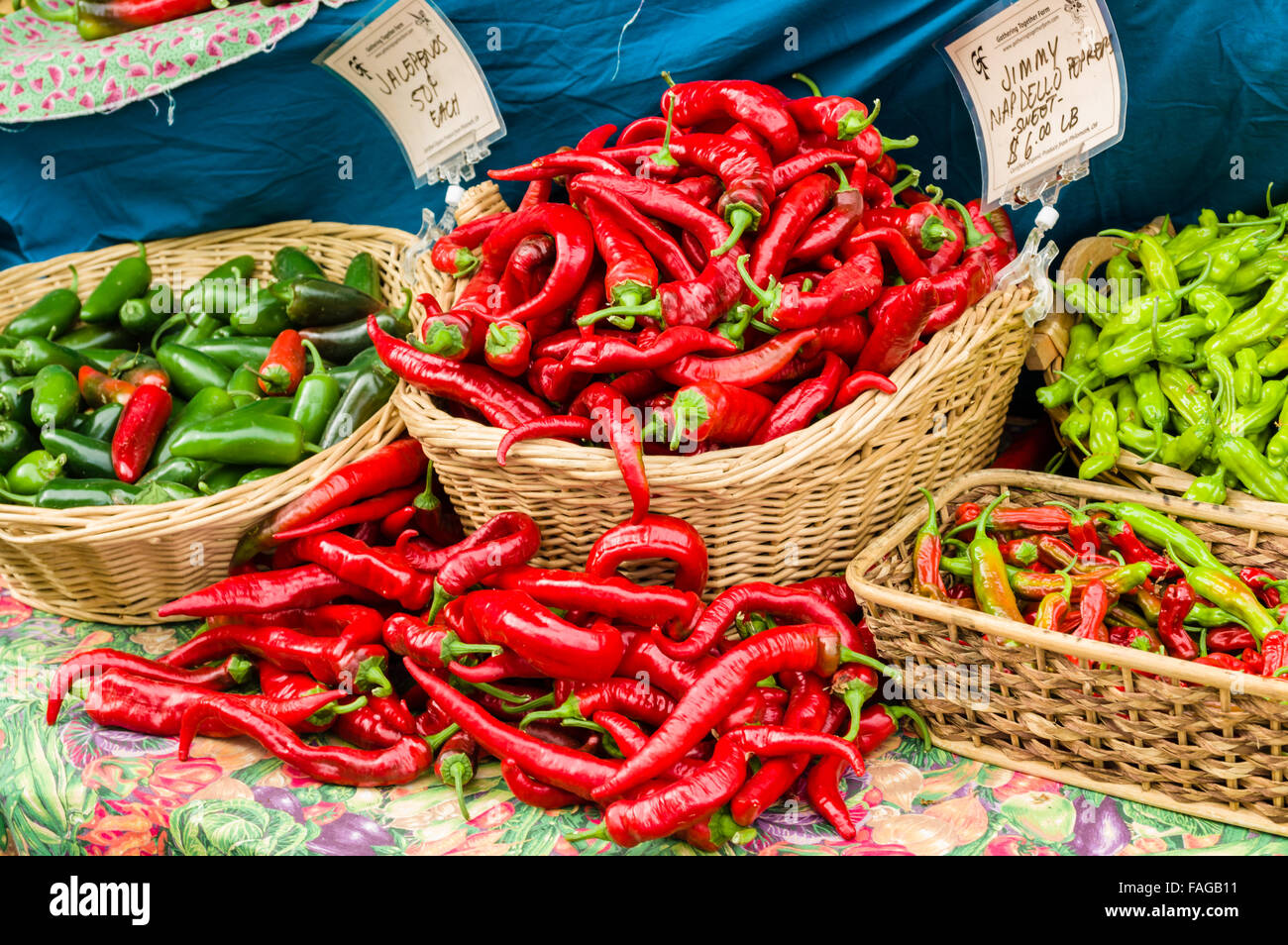 Baskets of red and green hot peppers on display at a farmer's market