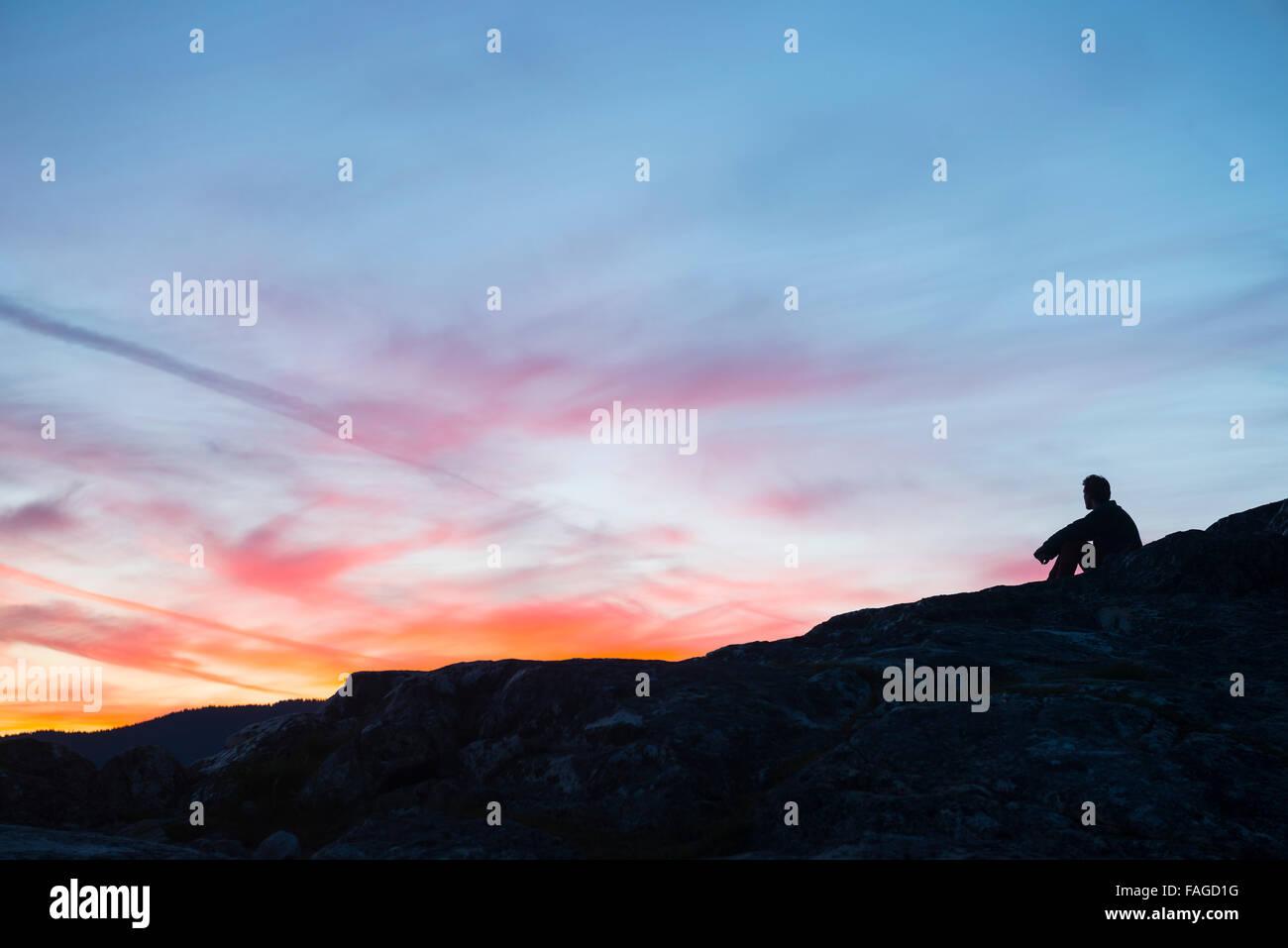 A lone man enjoying a beautiful sunset - Stock Image