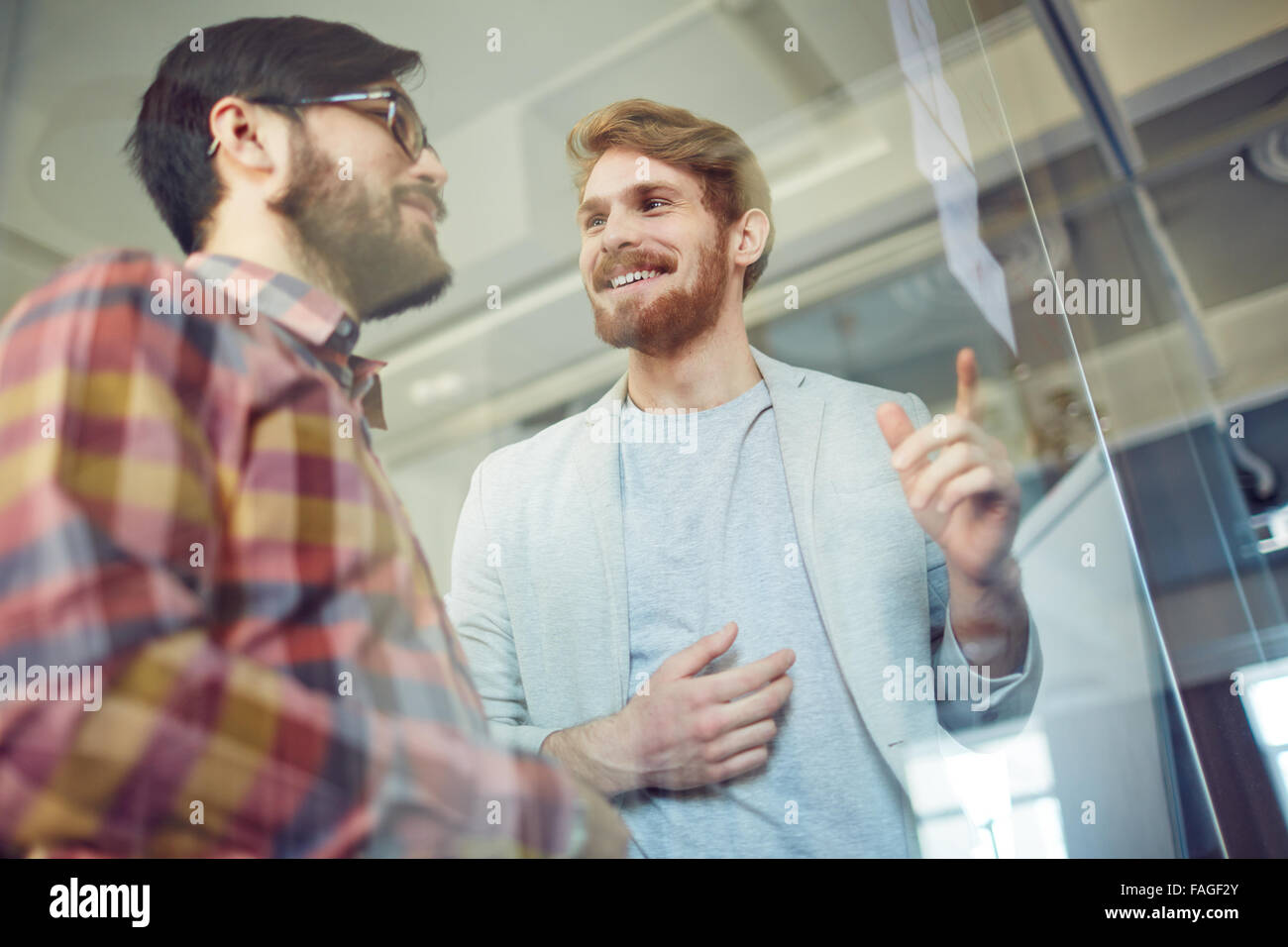 Happy office workers discussing notes at meeting - Stock Image