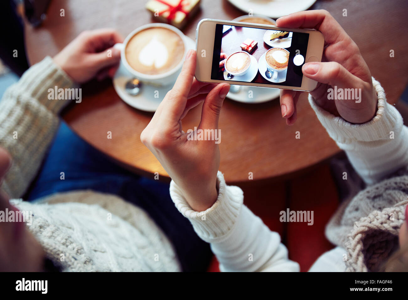 Girl holding smartphone with photo of two cups of coffee - Stock Image