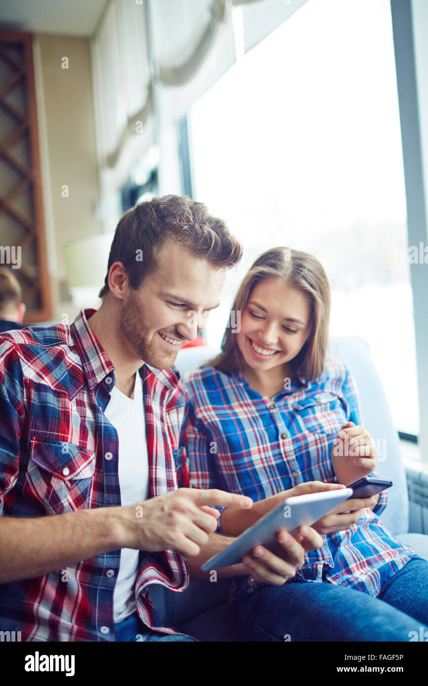 Young couple networking in cafe - Stock Image