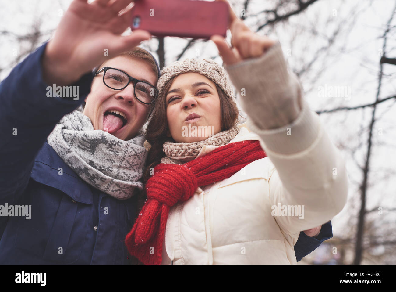 Young dates grimacing while making selfie - Stock Image