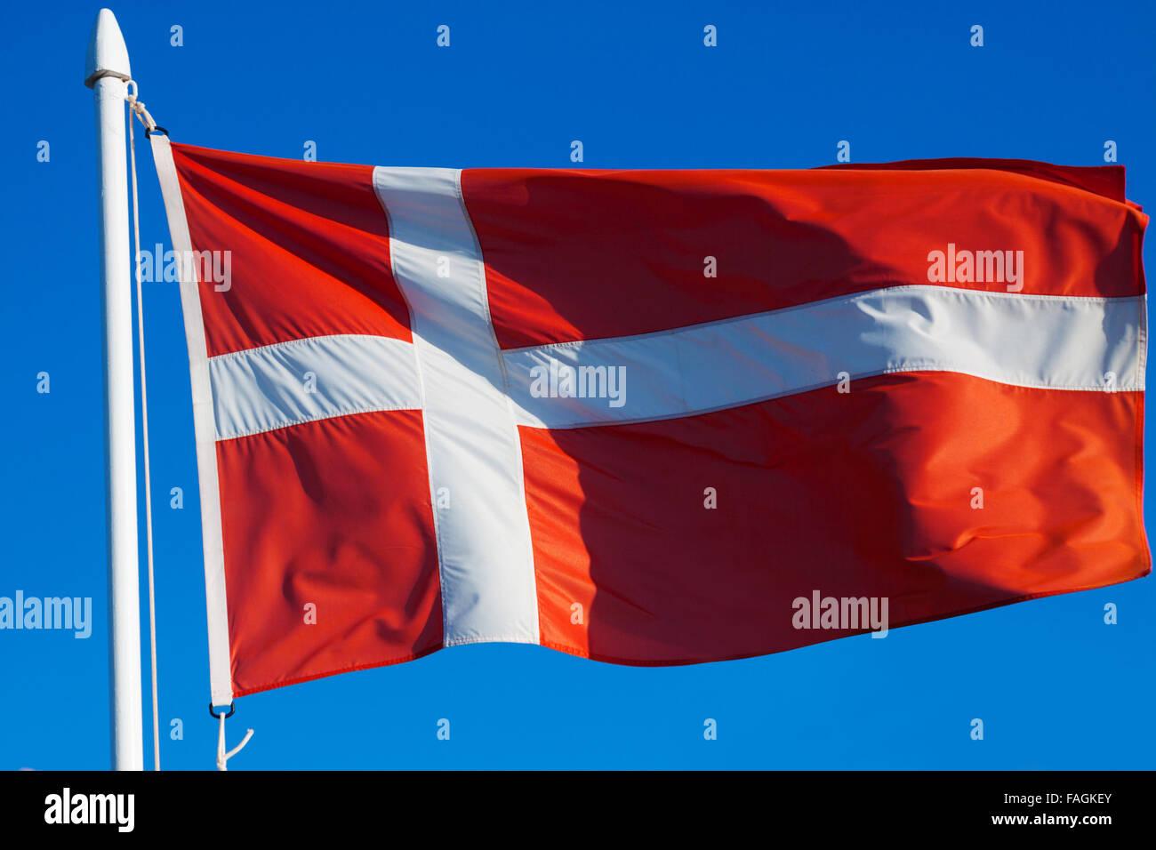 Flag of Denmark against blue sky - Stock Image