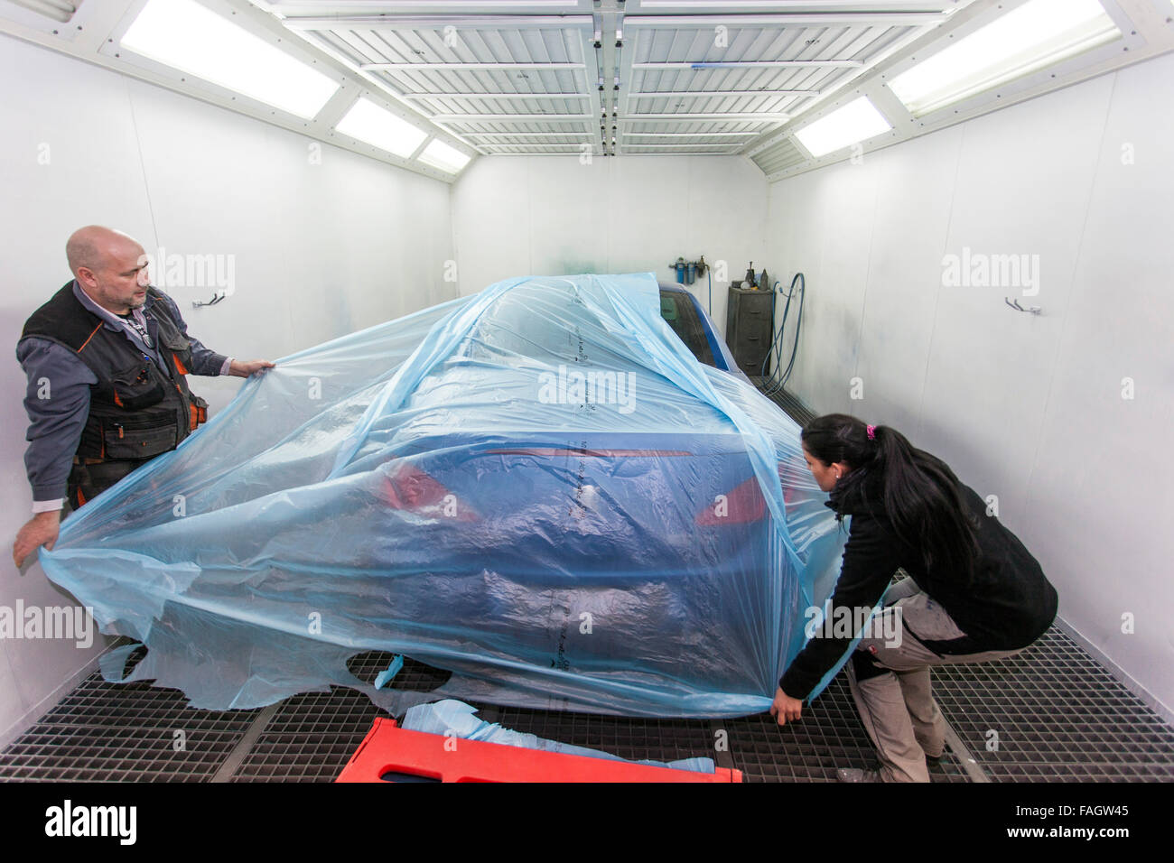 The vehicle is covered in front of the part paintwork. Stock Photo