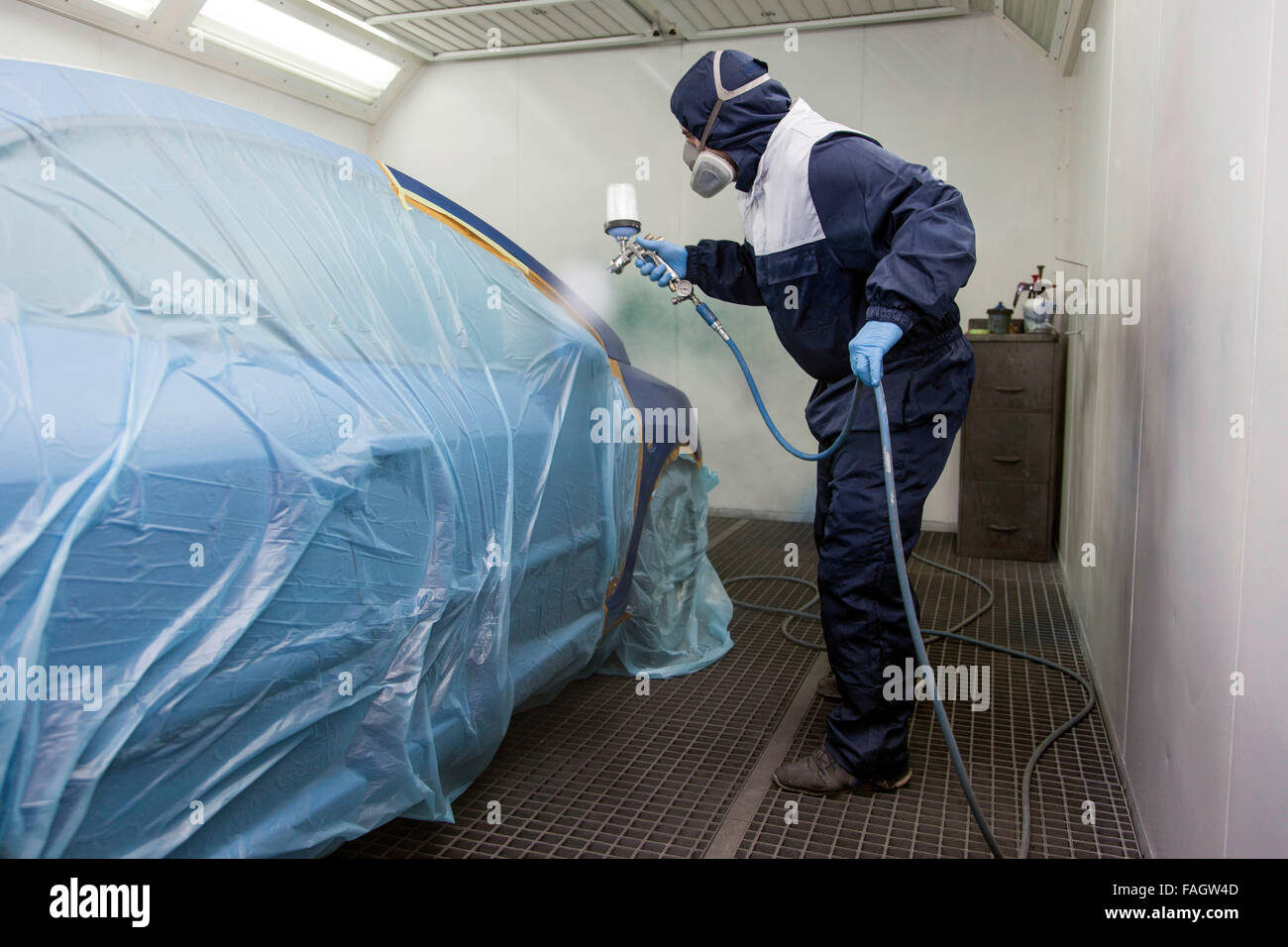 Vehicle varnisher in the paint spraying cabin. Stock Photo