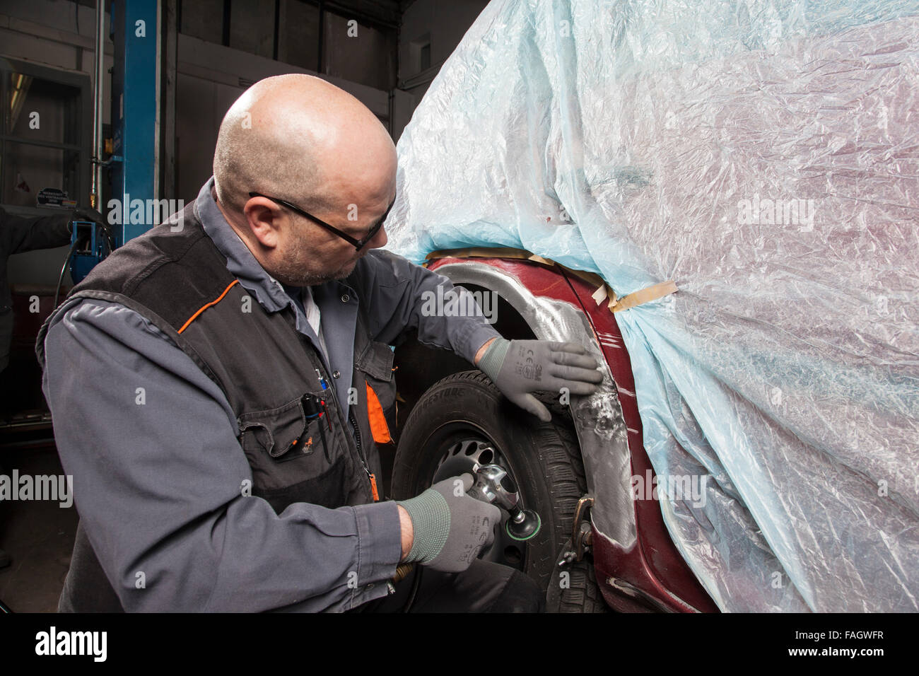 Car-body firm works on a wing with an angle grinder. - Stock Image