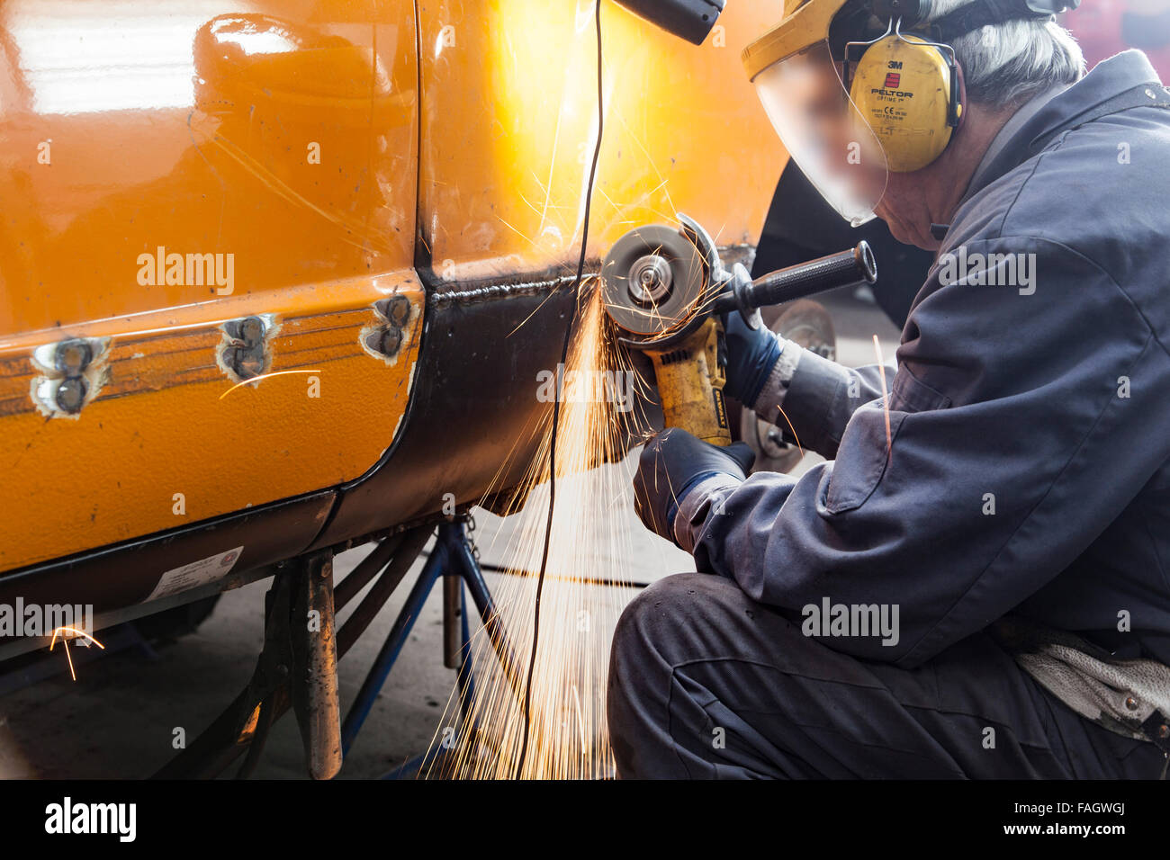 Coachbuilder restores a classic car VW Karmann Ghia. Welded seams are processed with angle grinder. - Stock Image