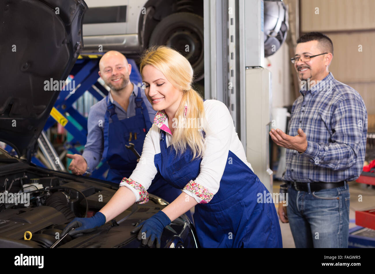 Female mechanic is fixing something under the hood of a car with a wrench while her colleague and owner are standing Stock Photo