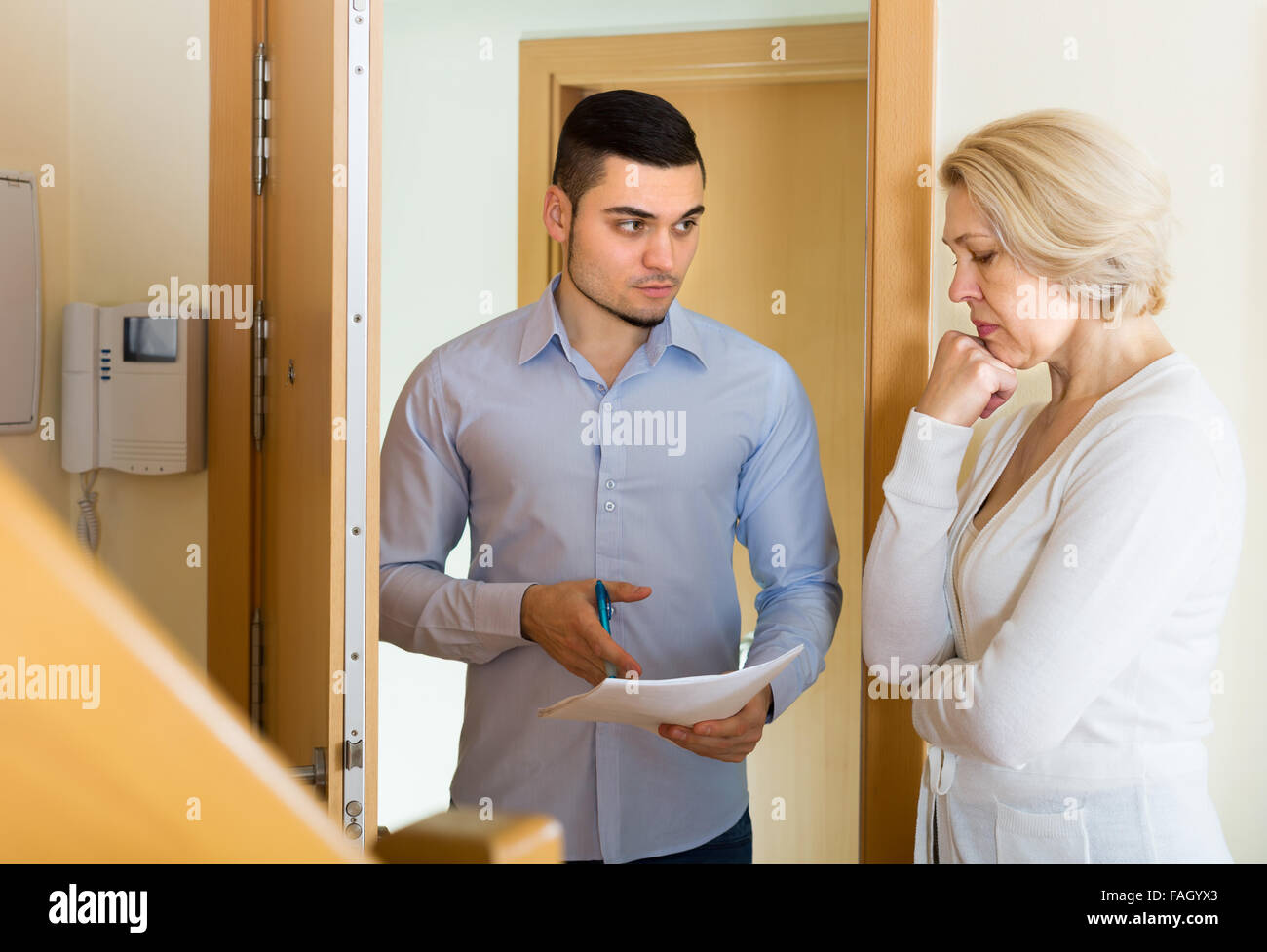 Businessman trying to collect money from housewife at home door Stock Photo