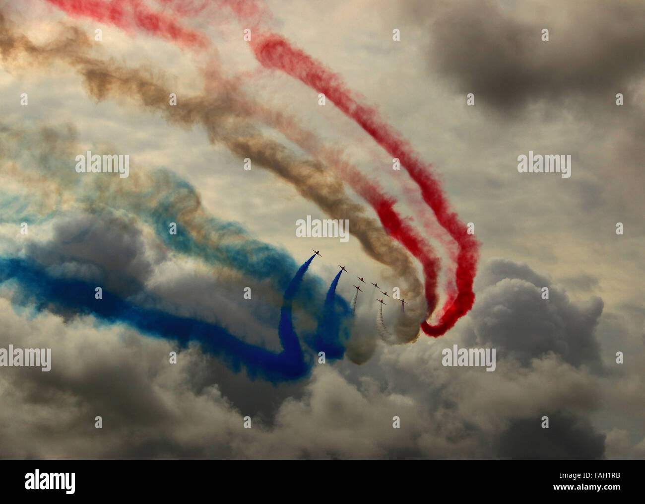 RAF Red Arrows Aerobatic Display Team paint a stormy sky with red white and blue smoke. - Stock Image