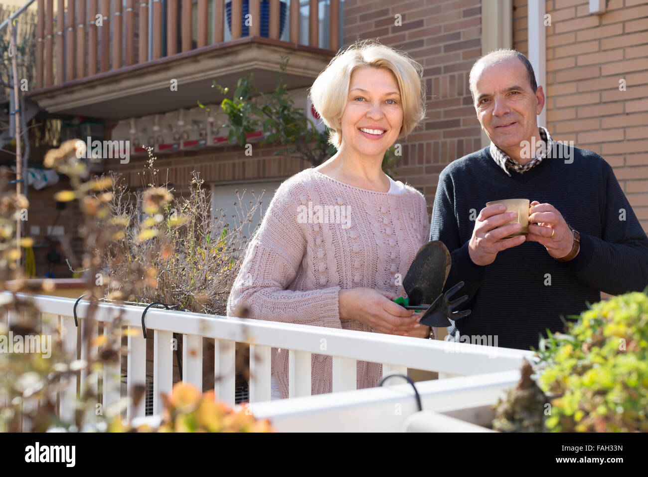 Happy smiling aged woman with horticultural sundry and aged man drinking tea in patio. Focus on woman Stock Photo