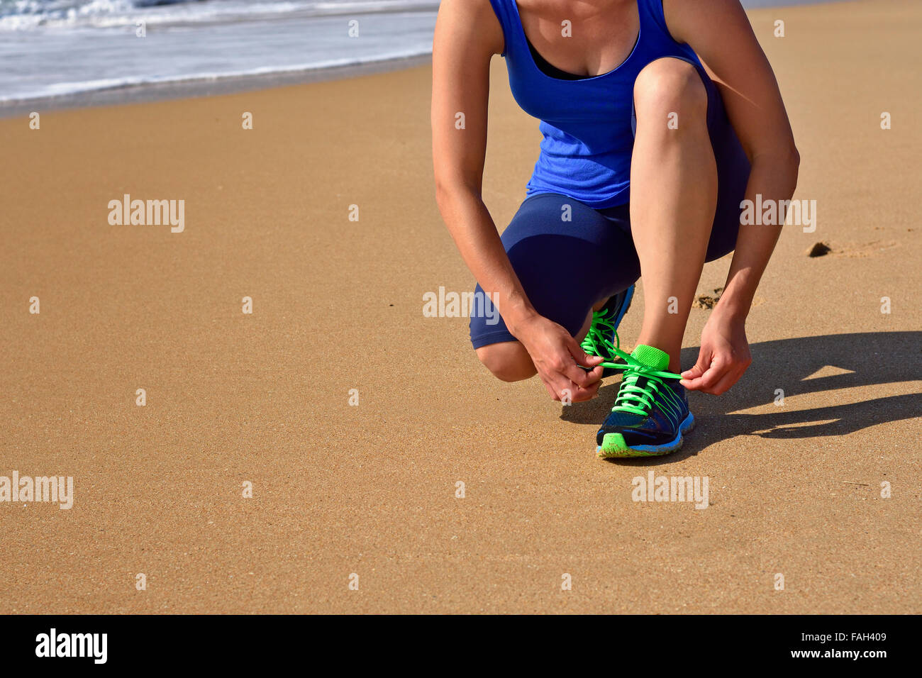 Running shoes - closeup of woman tying shoe laces. Female runner jogging getting ready for jogging on ocean beach. Stock Photo