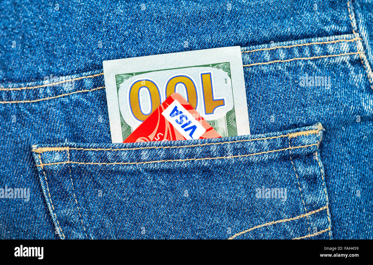 One hundred dollars bill and Credit card Visa sticking out of the back jeans pocket - Stock Image