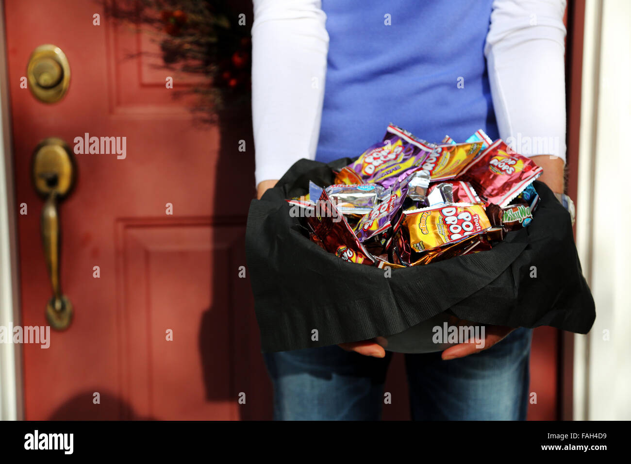 A woman standing outside her front door holding a bowlful of sweets and candy's for children calling to trick - Stock Image