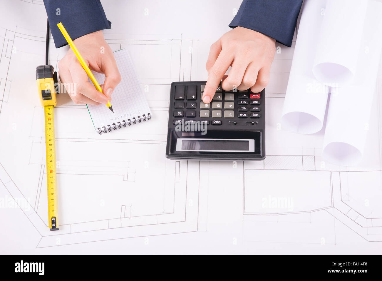 Male hands making measurement calculations. - Stock Image