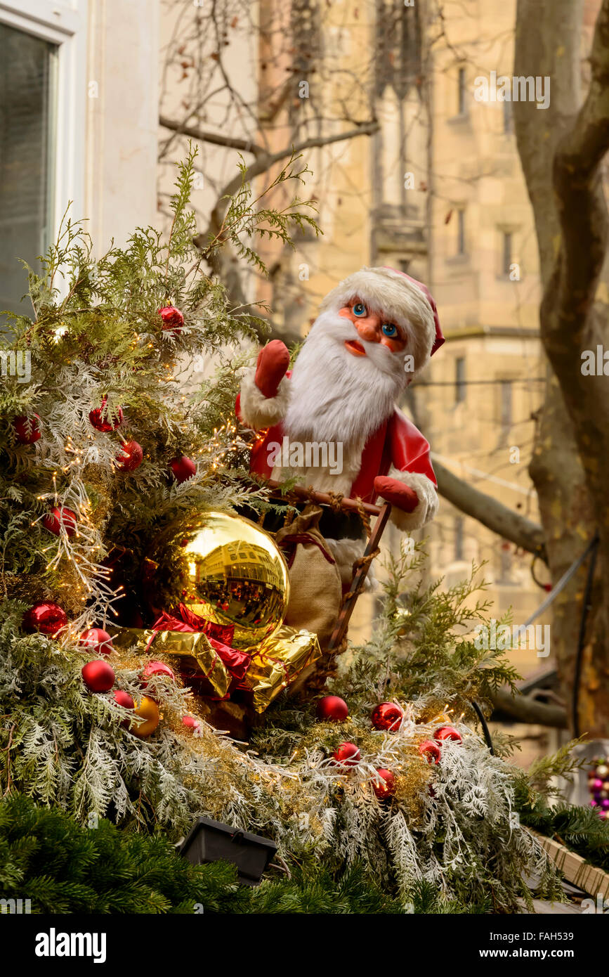 a golden glass ball and a Santa puppet on roof of Christmas market stall,  Stuttgart, Germany Stock Photo