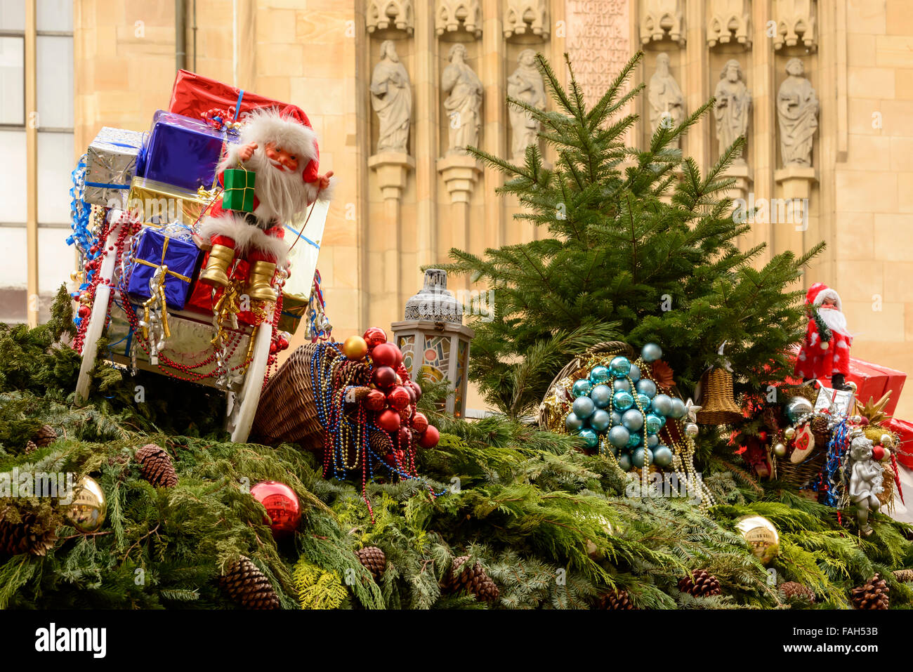glass balls and a Santa puppet between spruce branches on roof of Christmas market stall,  Stuttgart, Germany Stock Photo