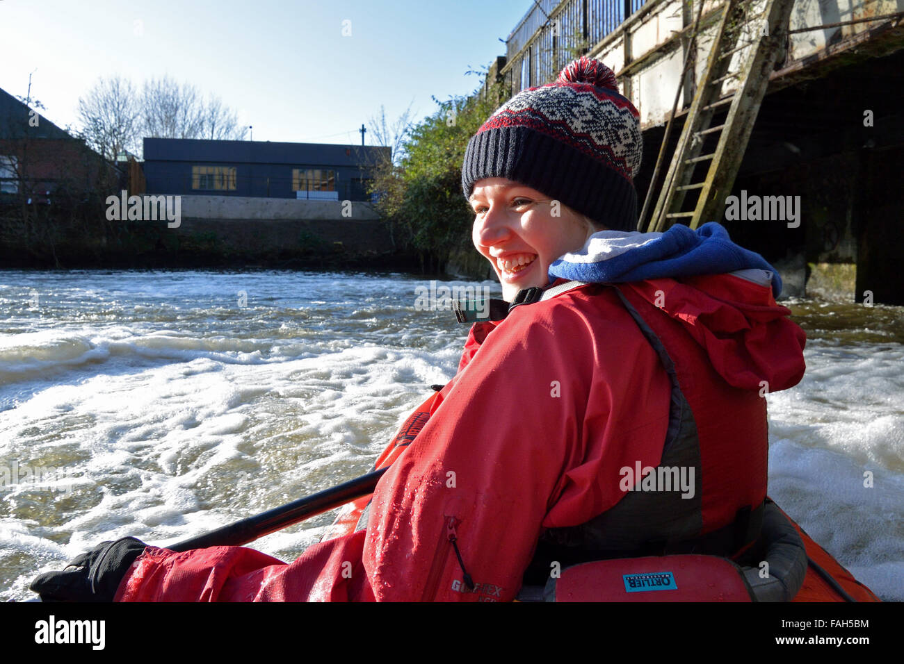 Young woman white water kayaking on the River Wensum in Norwich, at the head of navigation, New Mills Stock Photo