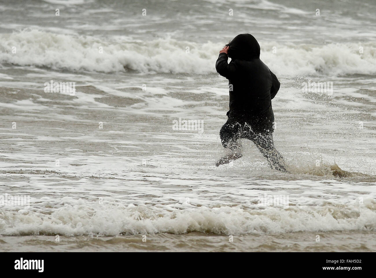 Boy in the sea fully clothed during stormy weather - Stock Image