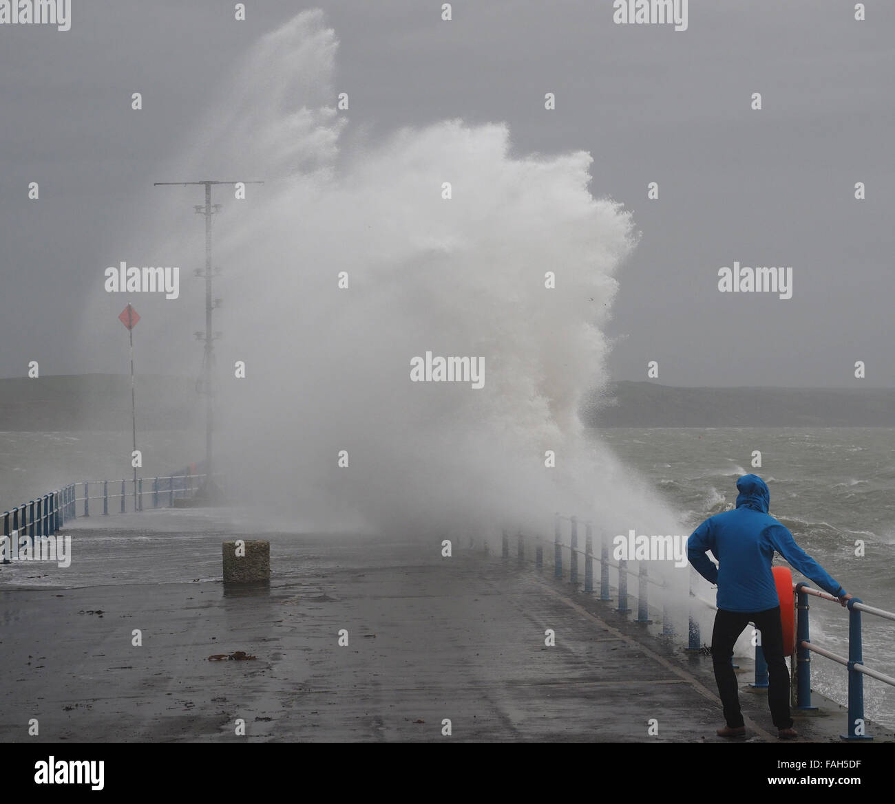 Dorset, UK. 30th Dec, 2015. Taking risk as this wave watcher at The Stone Pier in Weymouth Dorset was getting close Stock Photo