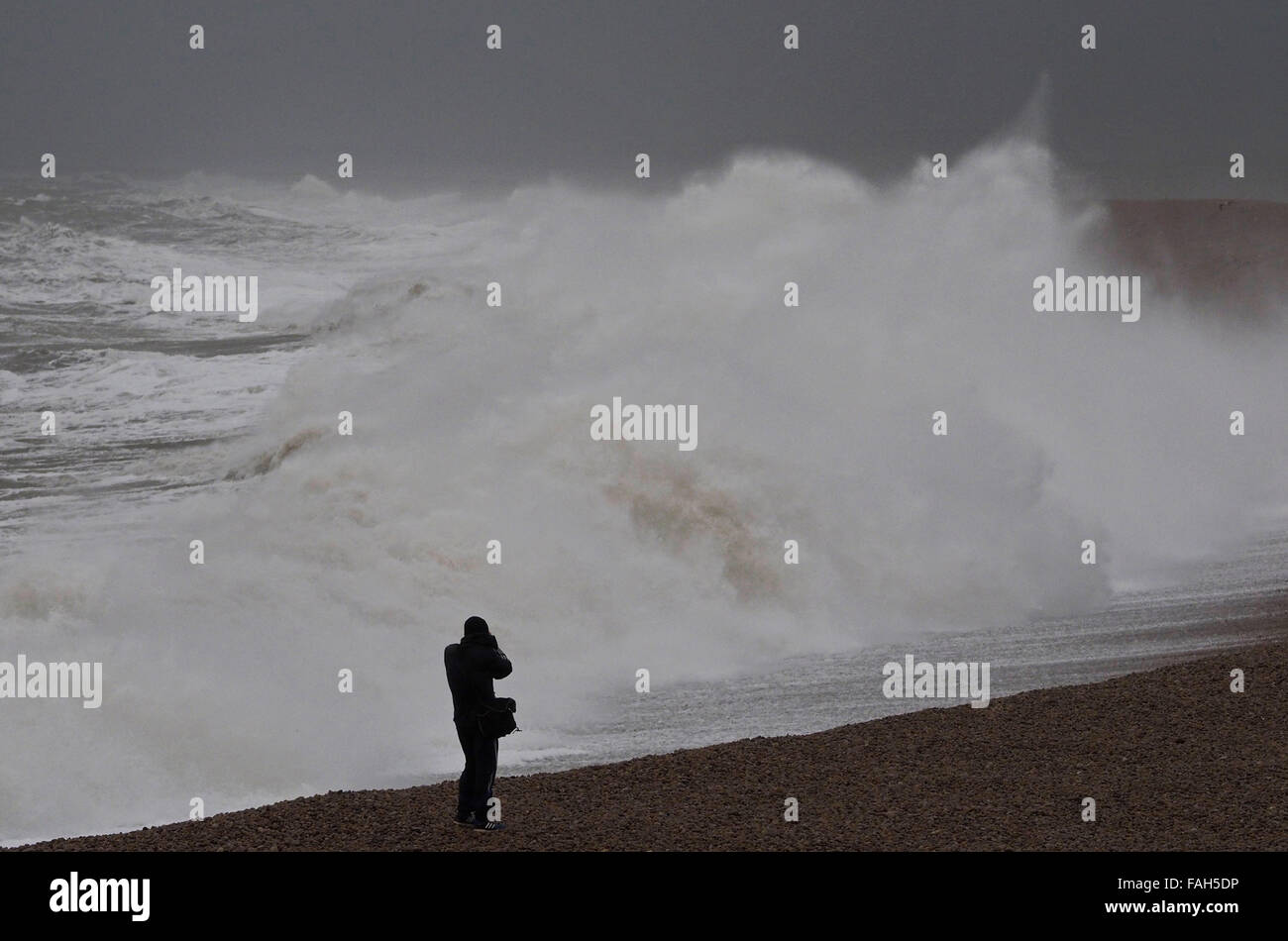 Dorset, UK. 30th Dec, 2015. Taking snaps and taking risk as this wave watcher was caught by the sea at Chesil Cove, Stock Photo