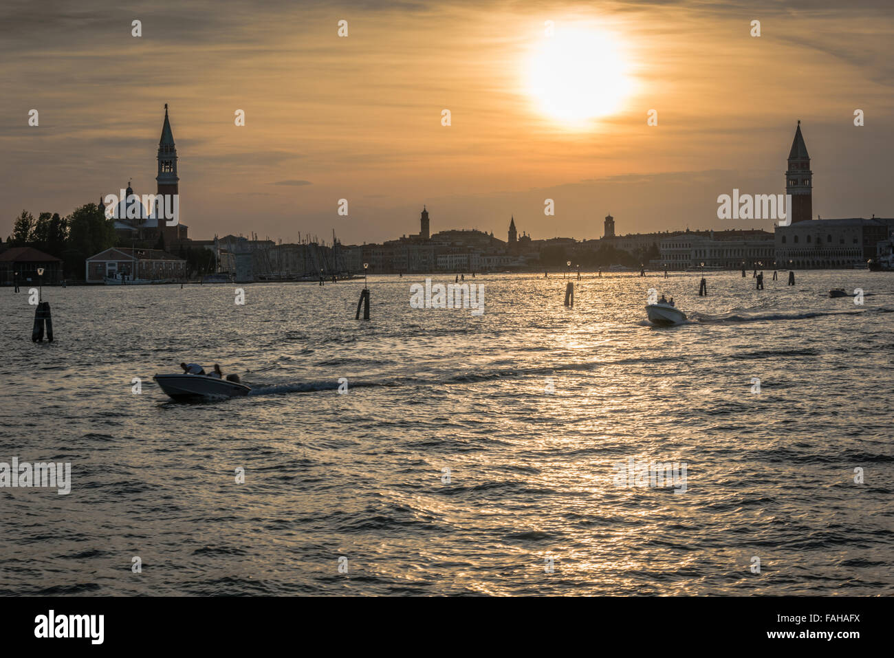 Stunning Sunset over the city of Venice as two speedboats cross the water Stock Photo