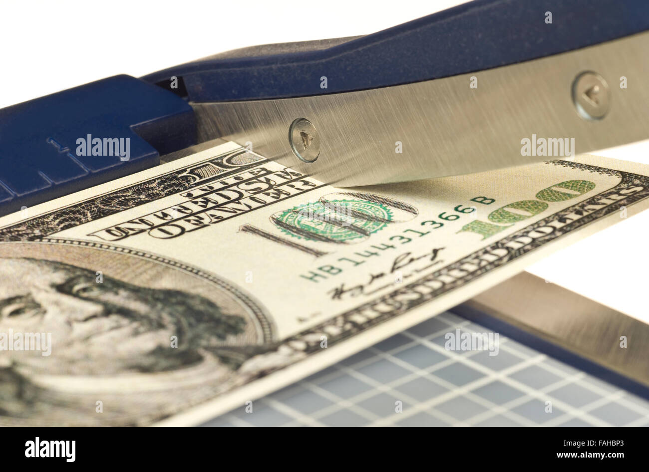 Paper Cutter Cutting off a piece of a One hundred dollar bill as an Inflation Illustration - Stock Image