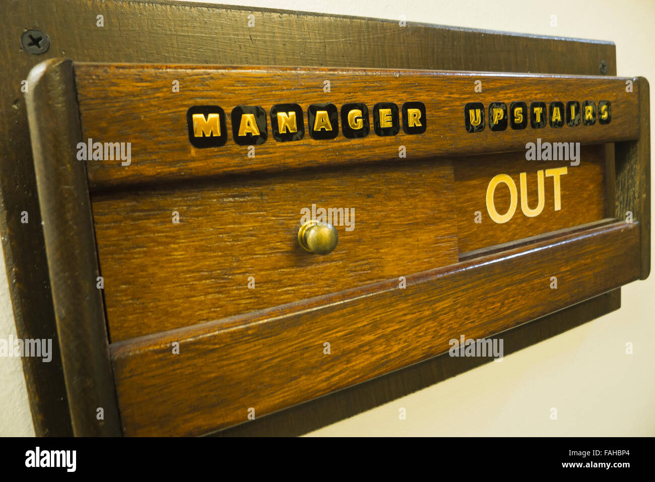 Wooden sliding sign 'MANAGER UPSTAIRS OUT'. - Stock Image