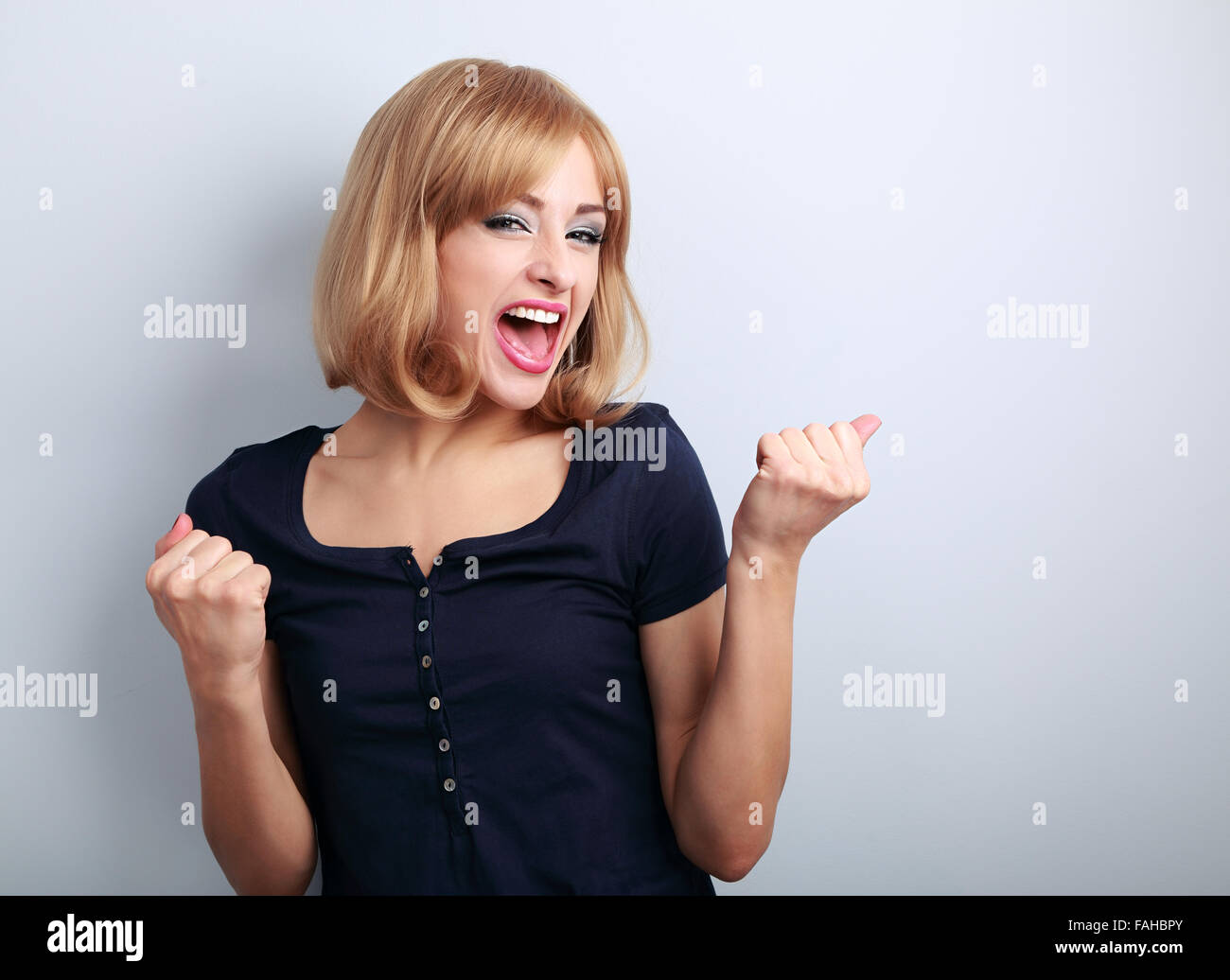 Happy excited winner woman with opened mouth. Happy blond young satisfacted girl showing the gesture yes by fists - Stock Image