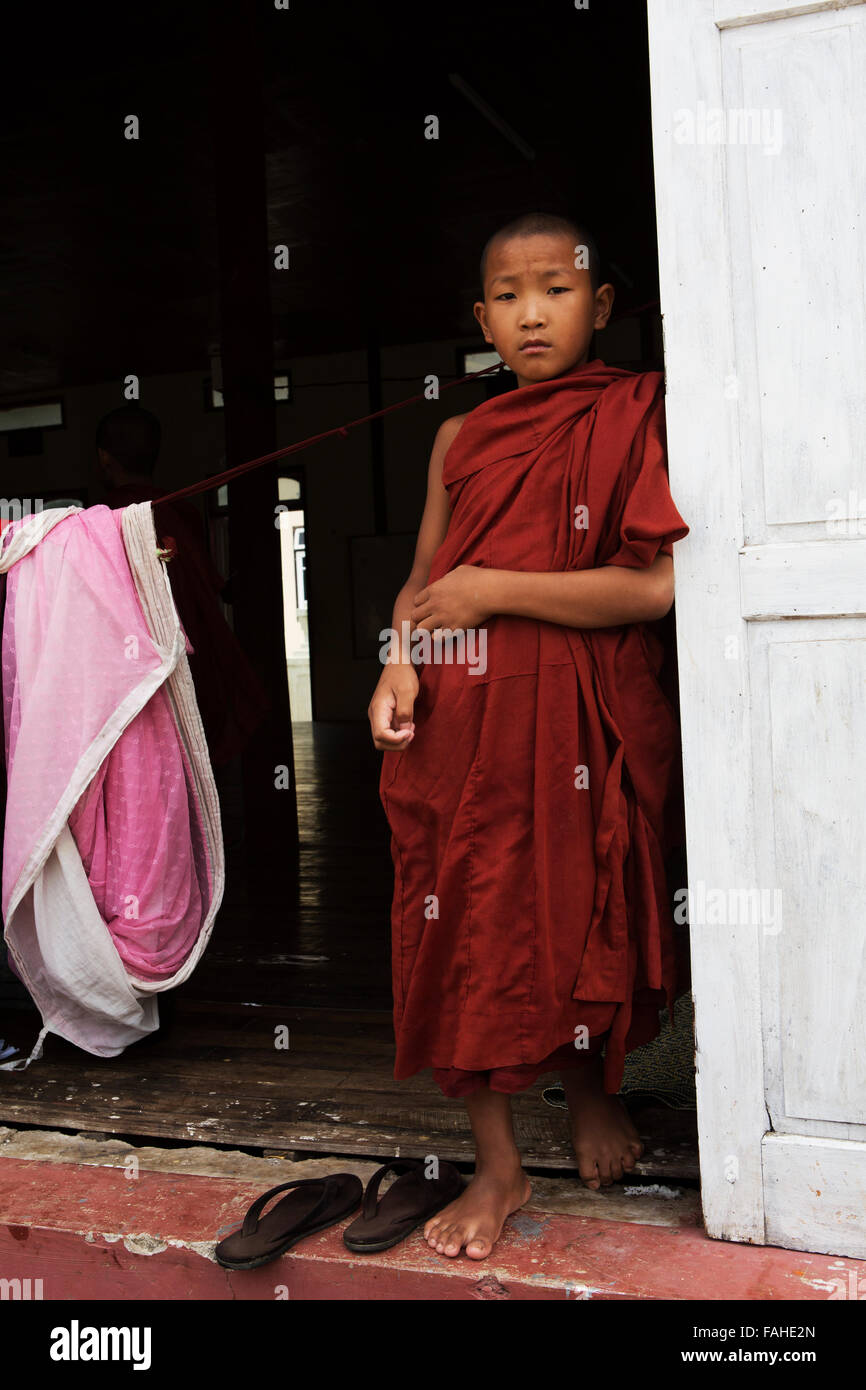 A young Buddhist monk at Shwe Yan Pyay Monastery at Taunggyi, Myanmar (Burma). The lad wears maroon robes. - Stock Image