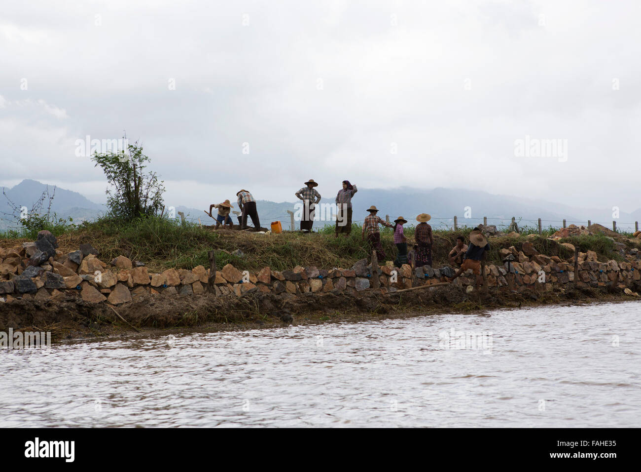 Labourers work by a tributary leading to Inle Lake in Myanmar (Burma). The lake and the surrounding area are heavily - Stock Image