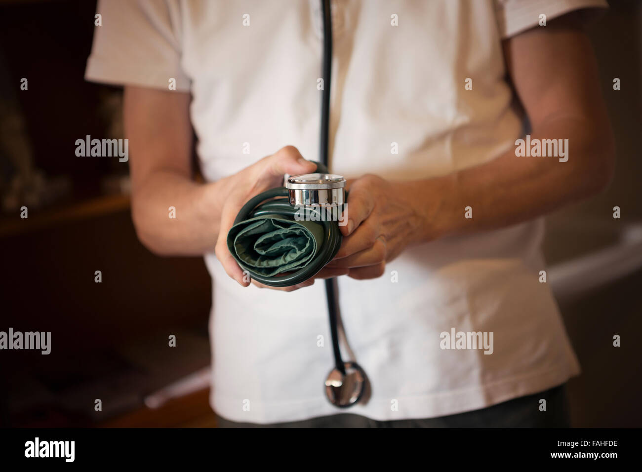 Doctor holding a blood pressure cuff and wearing a stethoscope - Stock Image