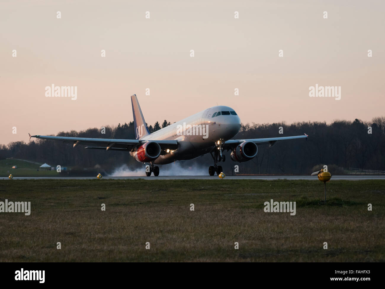 Smoke from burnt rubber is raising from the tires of an Airbus passenger aircraft right after touchdown at Zurich - Stock Image